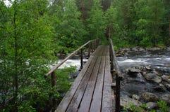 Puente de madera sobre el río pedregoso imagenes de archivo