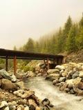 Puente de madera sobre rápidos de las montañas en el río rápido de la montaña en las montañas Imagenes de archivo