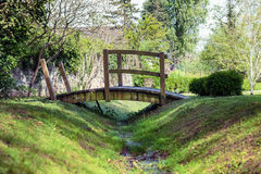 Puente de madera sobre una corriente en el parque Imagen de archivo libre de regalías