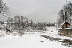 Puente de madera suspendido sobre un río de la montaña del invierno Foto de archivo