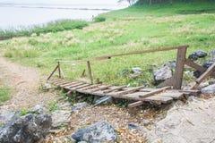 Puente de madera viejo abajo a la hierba del campo al lado del reservior Fotografía de archivo libre de regalías
