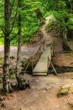 Puente de madera viejo sobre un pequeño río imagenes de archivo