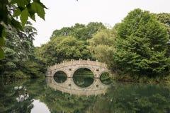 Puente de piedra chino con la reflexión simétrica en el lago Foto de archivo libre de regalías