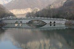Puente de piedra del arco de los lomos con la reflexión Fotografía de archivo libre de regalías