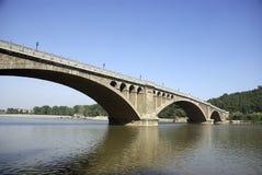 Puente de piedra del arco y cielo azul del color Fotografía de archivo libre de regalías