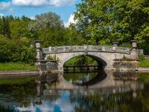 Puente de piedra en el lago en el parque en verano Imagen de archivo libre de regalías