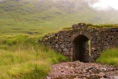 Puente de piedra en montañas escocesas imagen de archivo