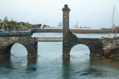 Puente de piedra sobre el puerto y el mar imágenes de archivo libres de regalías