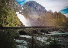 Puente de piedra viejo en un fondo de una cascada foto de archivo libre de regalías