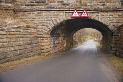 Puente de piedra viejo sobre un carril del país Fotos de archivo