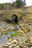Puente de piedra viejo a través de la pequeña corriente Fotos de archivo libres de regalías