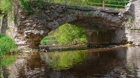Puente de piedra viejo a través de la pequeña corriente en el bosque Imagen de archivo libre de regalías