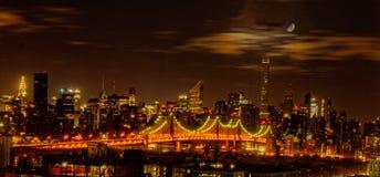 Puente de Queensboro visto en la noche con los gastos indirectos de la luna Fotografía de archivo