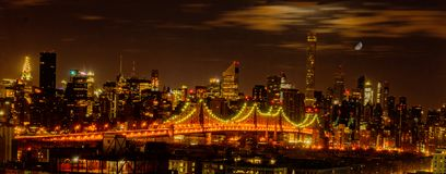 Puente de Queensboro visto en la noche con los gastos indirectos de la luna Imagen de archivo libre de regalías