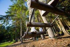Puente de registro de la travesía del hombre joven en bosque Imagen de archivo libre de regalías