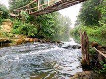 Puente de suspensión a través del río Imagenes de archivo