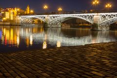 Puente de Triana by evening lights. Puente de Triana English translation: Triana Bridge with reflections in the Guadalquivir river during blue hour and a view on royalty free stock images