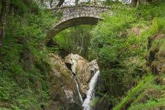 Puente del arco sobre la cascada en distrito del lago Fotografía de archivo