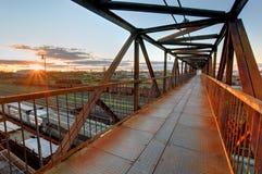 Puente del pie sobre ferrocarril en la puesta del sol Fotos de archivo