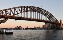 Puente del teatro de la ópera y del puerto del muelle del transbordador del punto de Milsons en la puesta del sol Imagen de archivo libre de regalías