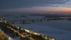 Puente del transporte con tráfico sobre el río congelado a la ciudad industrial grande en puesta del sol almacen de video