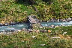 Puente destruido de madera viejo sobre el pequeño río de la montaña imágenes de archivo libres de regalías