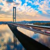 Puente en Kiev, la capital del automóvil y del ferrocarril de Ucrania Puente en la puesta del sol a través del río de Dnieper Pue Fotografía de archivo