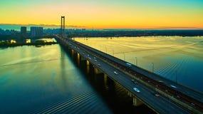 Puente en Kiev, la capital del automóvil y del ferrocarril de Ucrania Puente en la puesta del sol a través del río de Dnieper Pue Imagen de archivo libre de regalías