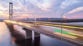 Puente en Kiev, la capital del automóvil y del ferrocarril de Ucrania Puente en la puesta del sol a través del río de Dnieper Pue Fotografía de archivo libre de regalías