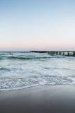 Puente en la playa en la puesta del sol Imágenes de archivo libres de regalías