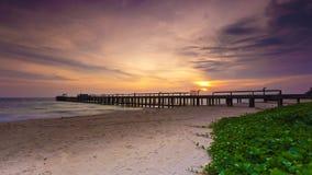 Puente en la playa en puesta del sol Imagen de archivo libre de regalías