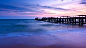 Puente en la playa en puesta del sol Fotos de archivo