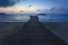 Puente en la playa en puesta del sol Imagen de archivo
