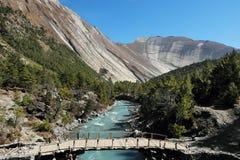 Puente en valle de la montaña en Himalaya nepalés Imagen de archivo libre de regalías
