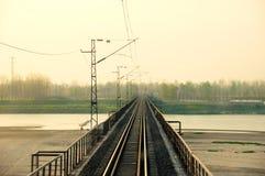 Puente ferroviario recto en la puesta del sol. Fotos de archivo libres de regalías