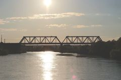 Puente ferroviario sobre el río en la puesta del sol Foto de archivo libre de regalías