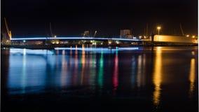 Puente iluminado y reflexión de luces en el agua del puerto de Tarragona, España Foto de archivo