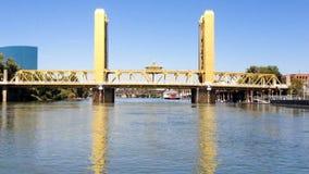 Puente inminente de la torre de Sacramento del barco en el río metrajes