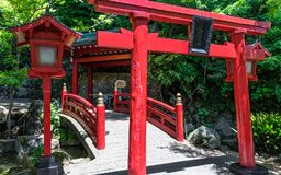Puente, linterna y Torii rojos tradicionales a la capilla sintoísta japonesa de Jigoku Meguri enmarcada por un paisaje verde En  fotografía de archivo libre de regalías