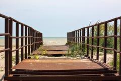 Puente oxidado viejo abandonado que lleva en el mar Foto de archivo