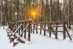 Puente peatonal en un parque nevoso en la puesta del sol Imagen de archivo libre de regalías