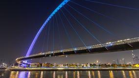Puente peatonal futurista sobre el canal del agua de Dubai iluminado en el hyperlapse del timelapse de la noche, UAE almacen de metraje de vídeo