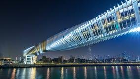 Puente peatonal futurista sobre el canal del agua de Dubai iluminado en el hyperlapse del timelapse de la noche, UAE metrajes