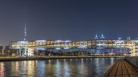Puente peatonal futurista sobre el canal del agua de Dubai iluminado en el timelapse de la noche, UAE almacen de metraje de vídeo