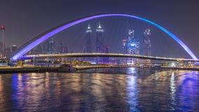 Puente peatonal futurista sobre el canal del agua de Dubai iluminado en el timelapse de la noche, UAE metrajes