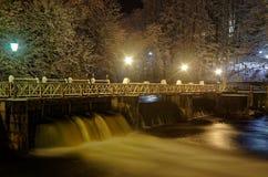 Puente peatonal sobre la pequeña presa en la noche, mún Lauterberg, Alemania fotografía de archivo