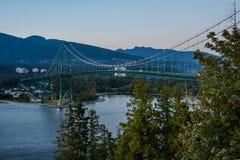 Puente, puesta del sol y tarde de la puerta de los leones en Vancouver, Canadá Fotos de archivo libres de regalías