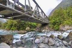Puente que atraviesa una corriente corriente azul clara Imágenes de archivo libres de regalías