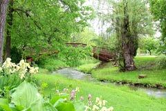 Puente que camina sobre pequeña corriente en parque imágenes de archivo libres de regalías