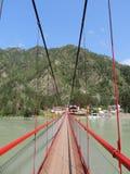 Puente rojo del paisaje sobre el río de la montaña Fotografía de archivo libre de regalías